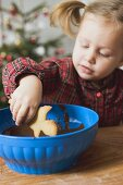 Girl dipping Christmas biscuit into chocolate icing