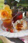 Rose hip jam on bread roll, rose hip tea, yellow rose