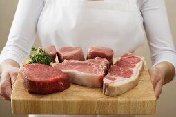 Person holding beef steaks & pork fillet on chopping board