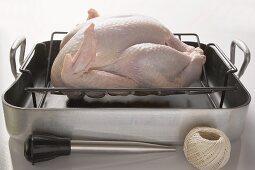 Chicken in roasting tin,  kitchen utensils beside it