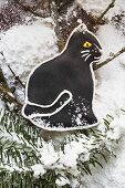 Black gingerbread cat with fir branches