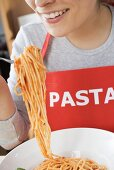 Young woman in apron eating spaghetti with tomato sauce