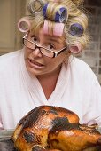 Horrified housewife with burnt turkey