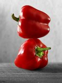 Two red peppers, one on top of the other