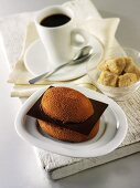 Small chocolate cake, cup of coffee and sugar cubes