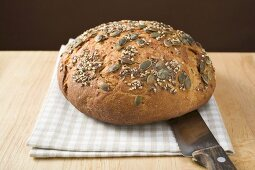 Wholemeal bread with pumpkin seeds on tea towel with bread knife