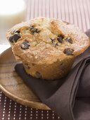 Chocolate chip muffin on wooden plate with napkin