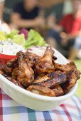 Person holding grilled chicken wings, people in background