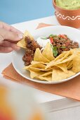 Hand dipping tortilla chip in mince sauce