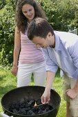 Couple having barbecue in garden (man lighting charcoal)