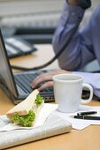 Businessman on phone, sandwich and coffee on desk