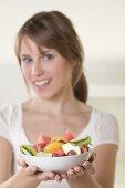 Woman holding dish of fruit salad