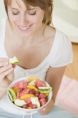 Woman eating wedge of apple from fruit salad