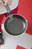 Footballer on Swiss flag holding frying pan