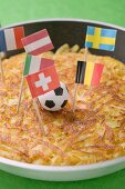 Rösti with toy football and European flags in frying pan