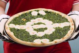 Female footballer holding spinach and mozzarella pizza