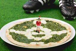 Spinach and mozzarella pizza, football boots in background