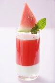 Watermelon drink with wedge of watermelon and mint leaves