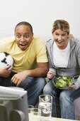 Couple in front of TV with football and salad