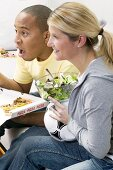 Couple in front of TV with pizza, salad and football