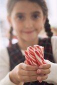 Girl holding several candy sticks