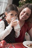 Girl drinking glass of milk at Christmas meal