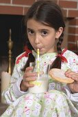 Girl drinking milk and holding biscuit
