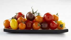 Tomatoes of various colours on wooden plate