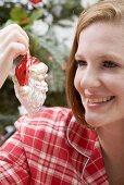 Woman holding Christmas tree ornament (Father Christmas)