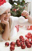 Woman in Father Christmas hat lying on carpet with Xmas baubles