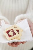 Woman holding jam biscuits on fabric napkin