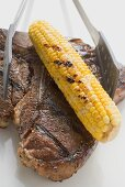 Grilled T-bone steak with corn on the cob and grill tongs