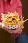 Woman holding nachos with melted cheese in cardboard container