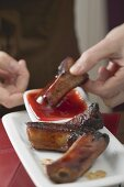 Woman dipping glazed pork rib in chilli sauce