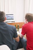 Two football fans watching football match on TV