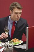 Businessman holding glass of white wine & working at laptop