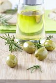 Olive oil, green olives and rosemary on chopping board