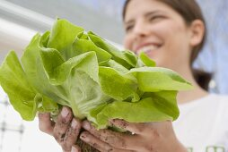 Young woman holding fresh lettuce from the garden
