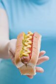 Woman holding hot dog with mustard, relish and ketchup