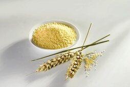 Couscous in small dish, ears of wheat beside it