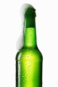 Beer frothing out of green bottle