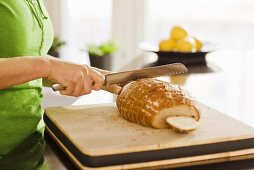 Woman slicing bread in a kitchen