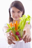 Girl holding a bowl of vegetable sticks with radishes
