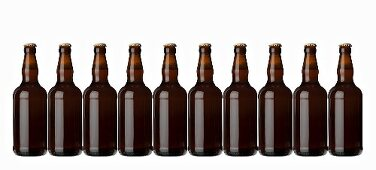 Ten brown bottles standing in a row (lager)
