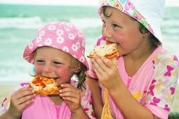 Children eating pizza by the sea