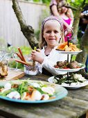 Little girl at smorgasbord in garden (Sweden)
