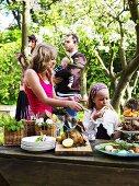 Family at smorgasbord in garden (Sweden)