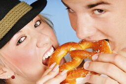 Young couple eating the same pretzel