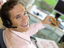 Young man with headphones eating pizza in office