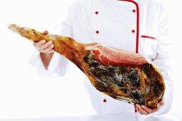 Cook holding serrano ham